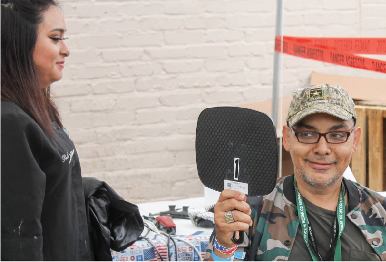 A stylist provides a mirror for a veteran after a haircut at the 2017 Stand Down for Veterans. At the yearly event, American GI Forum also provides flu shots, clothes, and emergency food.