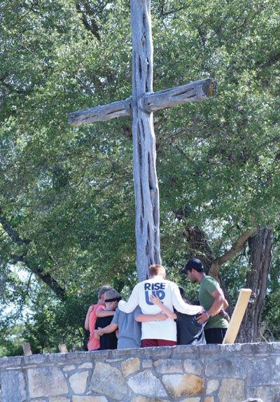 Campers pray at the cross during the Golgotha Run.