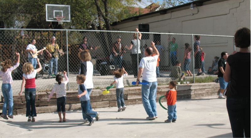 KidzTime volunteers and resident children dance to music on the playground at the Strong Foundation.