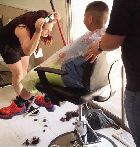 A volunteer gives a Strong Foundation resident child a fresh haircut.
